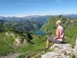 Junge Frau betrachtet Bergsee