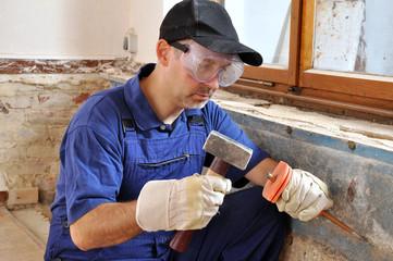 Handwerker mit Hammer und Meissel