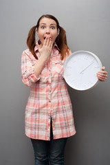 scared young woman showing wall clock