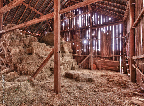 Leinwanddruck Bild Interior of old barn with straw bales