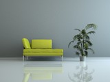 Wohndesign - grünes Sofa vor grauer Wand