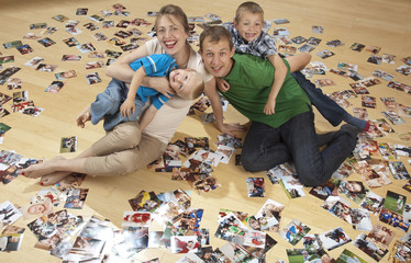 Family having fun on the floor and watching photos