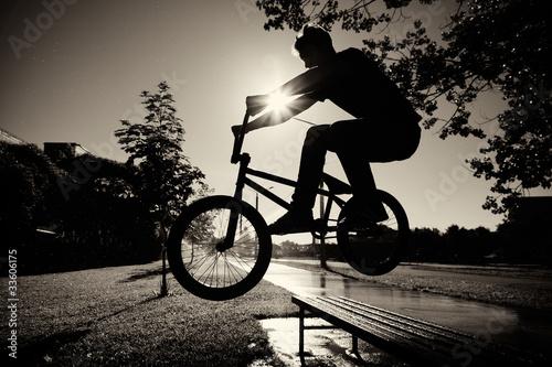 Leinwandbild Motiv boy jumping over bench  on bmx