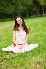 Beautiful smiling girl sits on green lawn