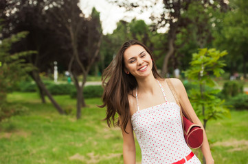 portrait of a beautiful young girl in a park on a background