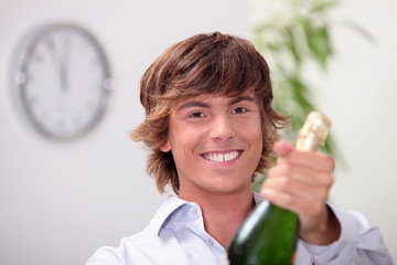 Young man with a bottle of champagne for new years's eve