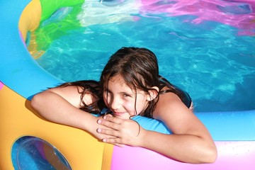 young girl playing in paddling pool on sunny day