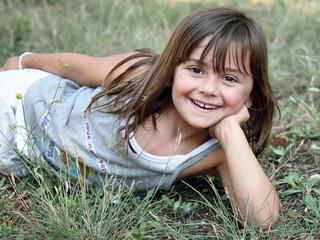 Petite fille allongée dans l'herbe (été 5-6 ans)