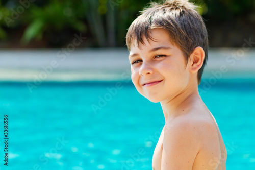 Happy young smiling boy by the pool