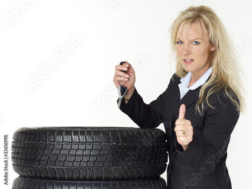 Woman next to winter tyres holding car key shows thumb up