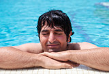 Man lieing with closed eyes and relaxing in swimming pool