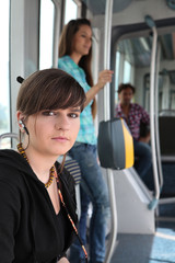 Photo of teenager riding the tram with passenger in background