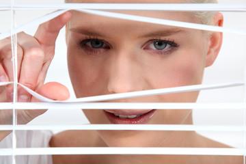 Woman peeking through some blinds