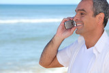Smiling man using a cellphone by the ocean