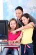 Teacher with kids in front of desktop computer