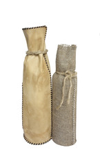 Bottles in leather and burlap gift bags, isolated over white