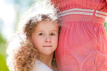 beautiful little daugher hugging her mother