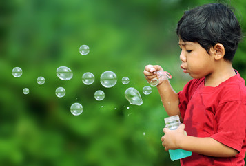 Cute young boy playing with soap bubbles