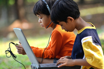 Boy and girl using Computer and gadget