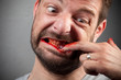 Crazy nailbiter. A man biting of his nails, fingers bloody