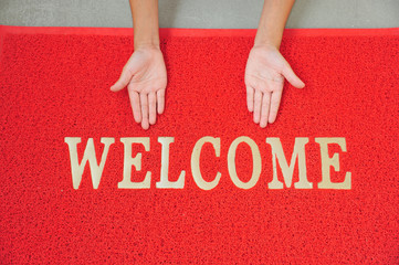 Hands In A Welcome Sign And A Red Floor Mat