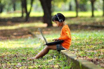 Little girl using laptop computer at a park
