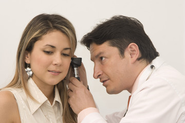 Doctor examining his beautiful patient's ears