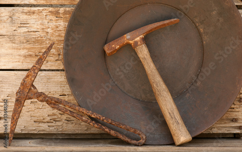 Old mining picks & gold pan against wood background.