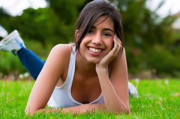 Chica tumbada en la hierba sonriendo