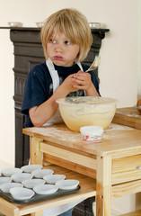 Cheeky boy tasting the cake mixture