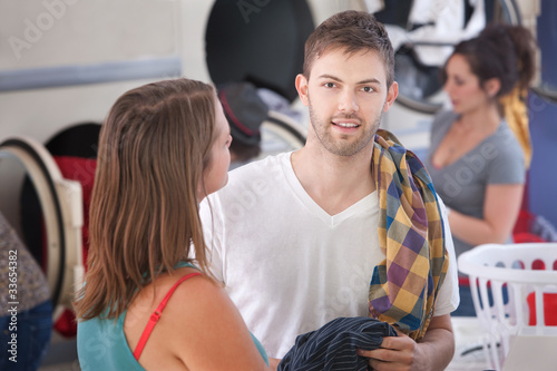 Young Man With Girlfriend In Laundromat
