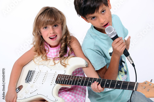 Little boy and girl playing musical instruments