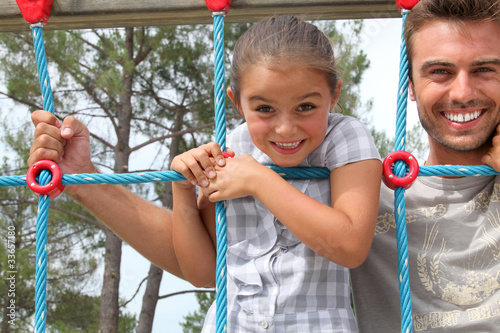 Young girl on a climbing frame with her dad