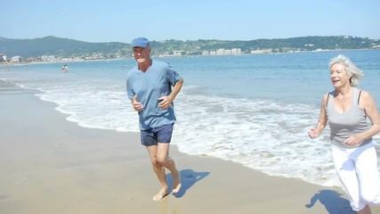 Senior couple jogging on a sandy beach