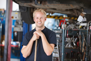 Smiling mechanic holding broom
