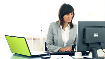 Busy businesswoman working on laptop and computer in the office