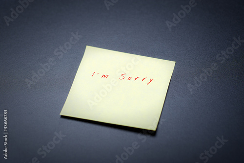 yellow postit with I'm sorry tect on a black board