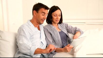 Couple in sofa using electronic tablet