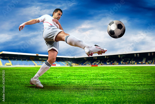 Fotobehang voetbal Happiness football player after goal on the field of stadium wit