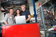 Smiling couple standing with mechanic using laptop
