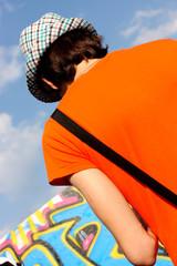 jeune au tee-shirt orange et chapeau