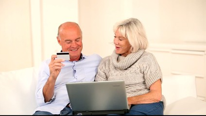 Senior couple doing online payment with touchpad