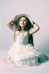 Beautiful child girl in elegant white dress and hat.