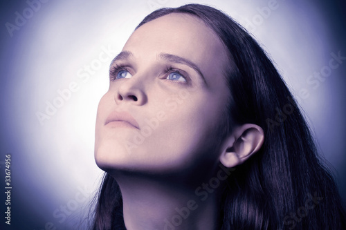 Young woman with blue dramatic eyes looking
