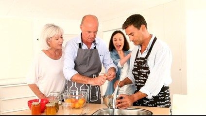 Family preparing fruit jam in home kitchen