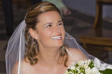 Sposa che sorride con il bouquet in chiesa