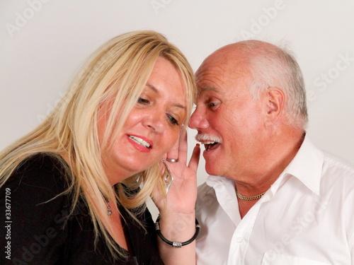 Leinwanddruck Bild Ein Mann flüstert einer Frau etwas ins Ohr