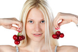 Female fooling with cherries holding them like earrings poster