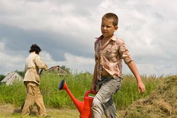 Мальчик с красной лейкой в огороде