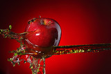 Fototapety red apple in juice stream